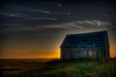 The sun rises behind the an old barn.