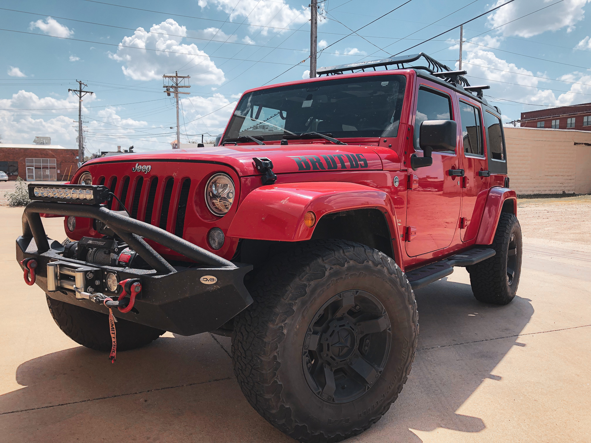 Red jeep parked at an angle on concrete pavement outside