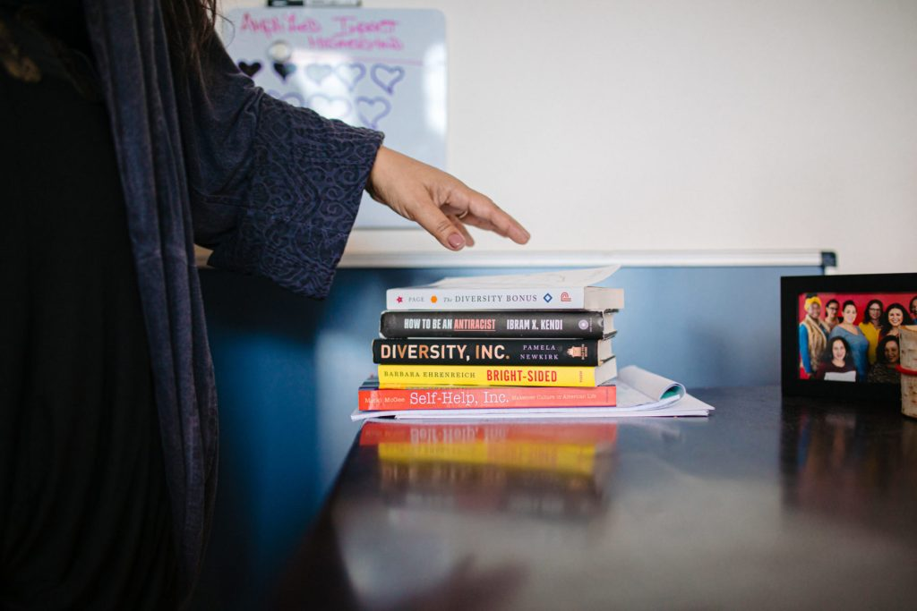 stack of books on Trudi's desk including Diversity, Inc., Bright-Sided, and How to be an Antiracist