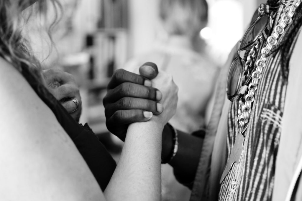 Close-up photo of two people, one Black one white, holding hands.