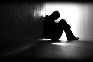 Silhouette of a man huddled in a corner of a hall looking emotional