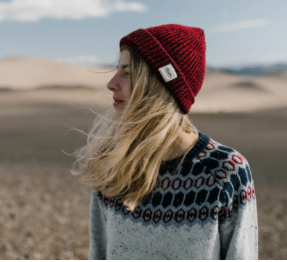 Girl in grey sweater with red, white and blue detail.