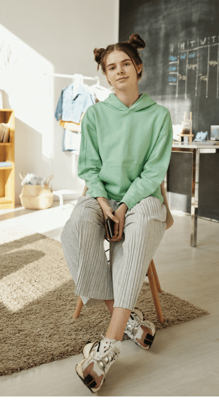 Casual outfit with grey cropped pants and a green sweat shirt.