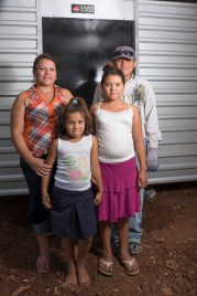 Laura, a single mom with three kids, in front of their new house!