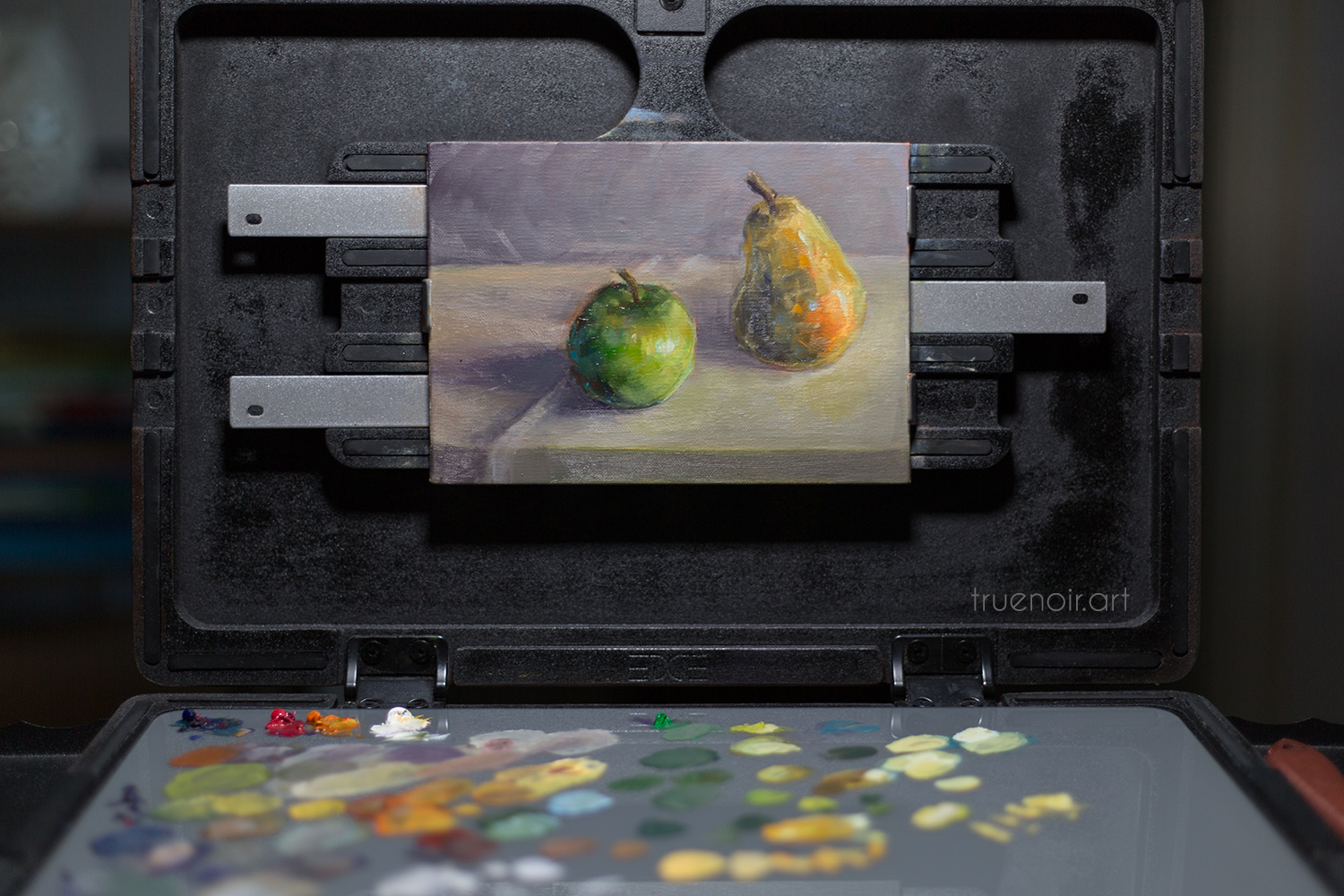 A still life painting of an apple and a pear on artist's easel.