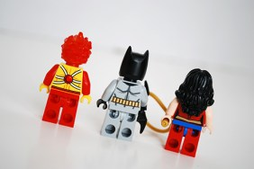 Rear view of Firestorm, Batman, and Wonder Woman.