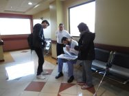 Dr. Asif Parkar meets with a patient and reviews her file. Local medical student, Juan, assists as translator.