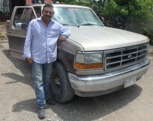 Juan stands beside his trusty pick up truck.