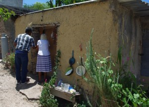 This elderly lady lives alone in a tiny one room adobe house.