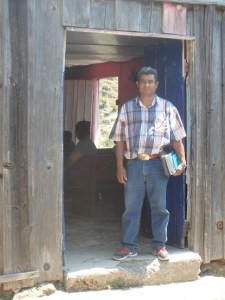 Martin stands at the door of the wooden church building before the service.