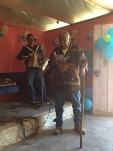 Juan plays the accordion as the Pastor's brother sings.