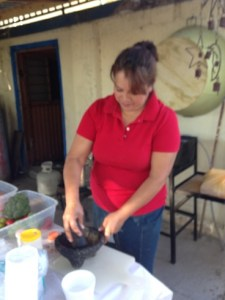 Sandra uses an old stone basin to make some fresh pepper sauce.