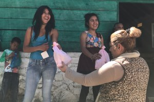 Ana hands some gifts to teen aged girls. Each gift included a Christian tract.