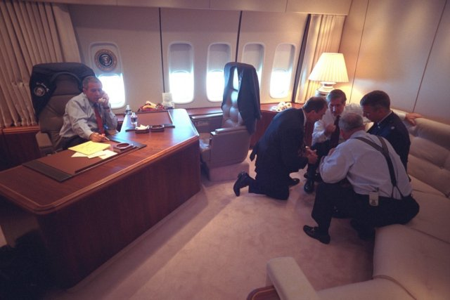 president-bush-talks-on-the-telephone-as-senior-staff-huddle-in-his-office