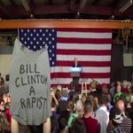 Bill Clinton heckled by woman holding sign calling him rapist