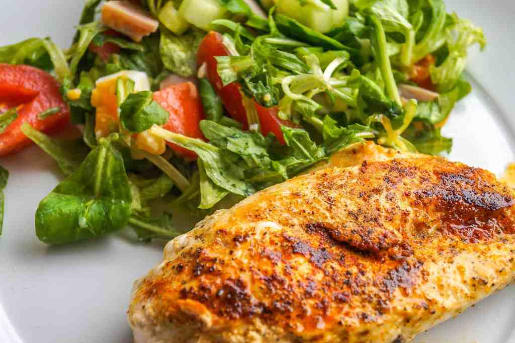 picture of chicken breast and a salad on a plate for dinner ideas in a muscle building diet