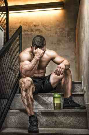 A fit male resting in between workouts per bodybuilding tips
