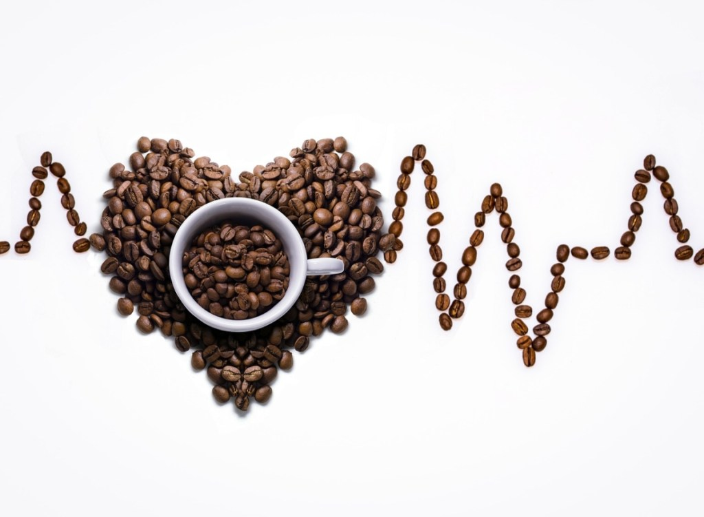 a picture of a heartbeat traced with coffee dicaffeine malate beans and in the center a pile of coffee anhydrous beans in the shape of a heart.