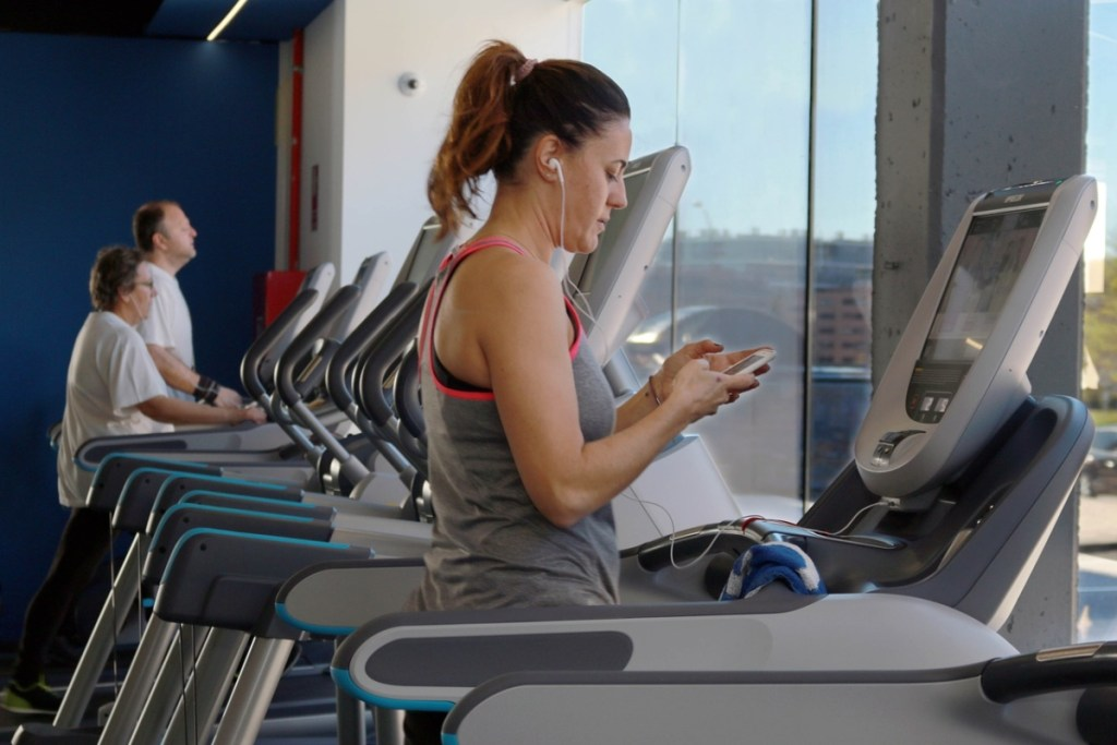 An older women on a treadmill at the gym performing liss cardio