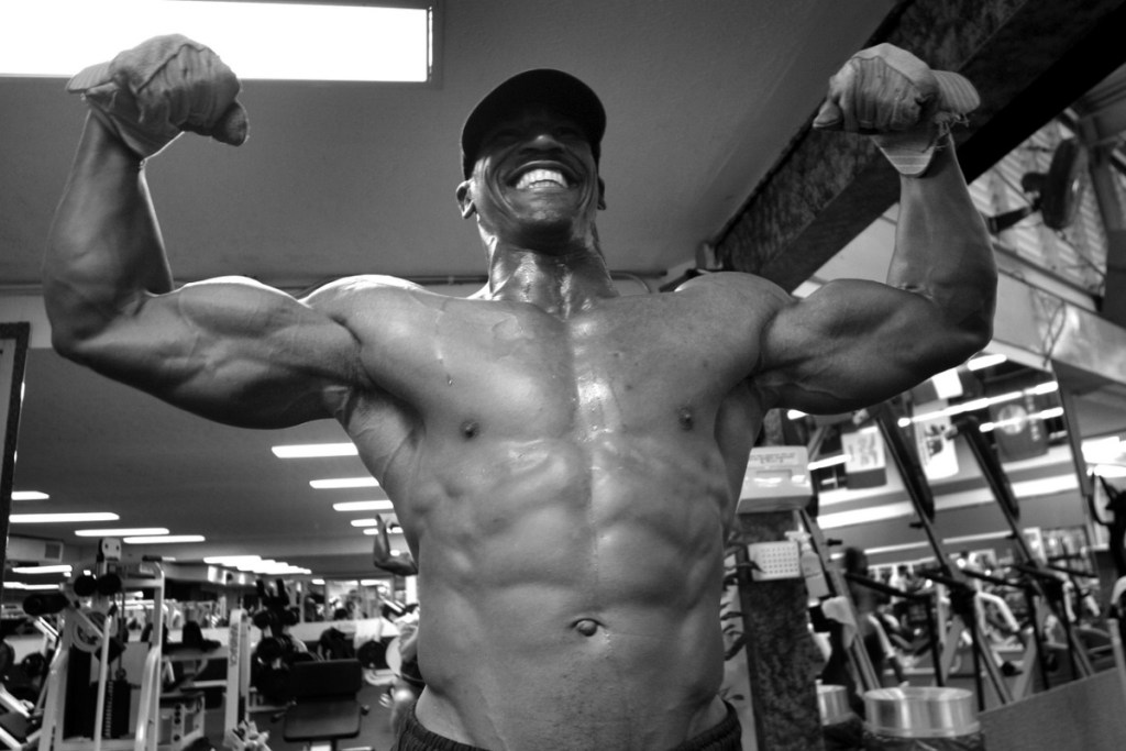 a young fit bodybuilder with abs and defined biceps and chest, showing you what results to expect from a muscle building diet.