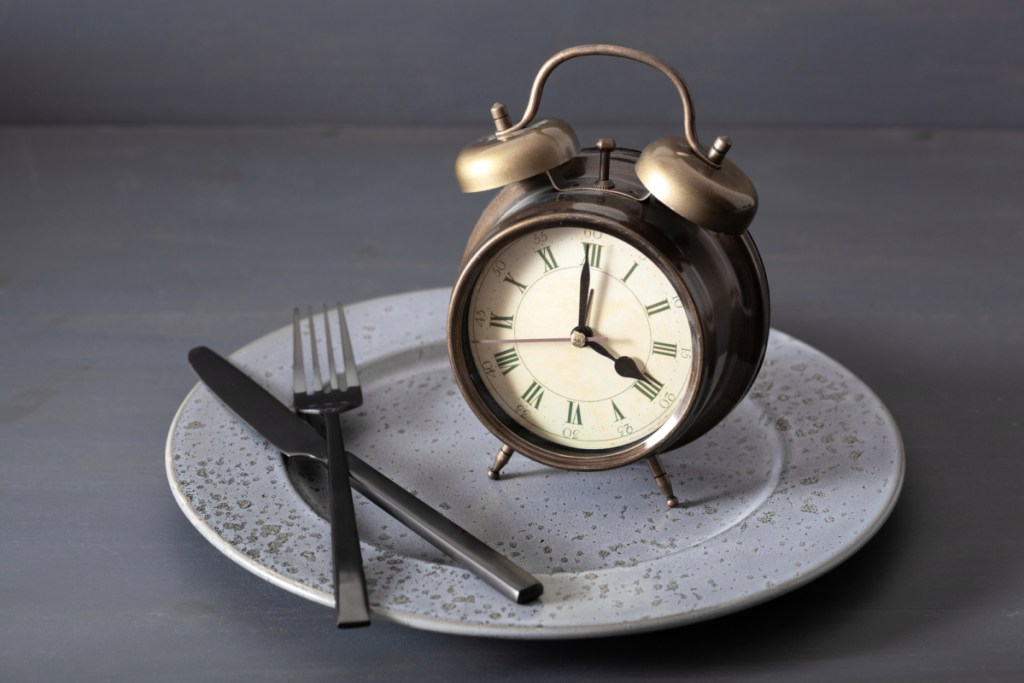 concept of intermittent fasting macros, weight loss. alarm clock fork and knife on a plate