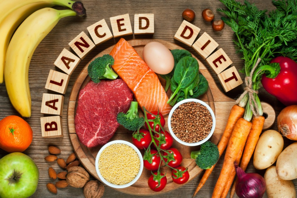 Balanced diet - healthy food on wooden table, referring to the ideal of eating the correct ratio of macronutrients to know how many calories you should eat to gain muscle