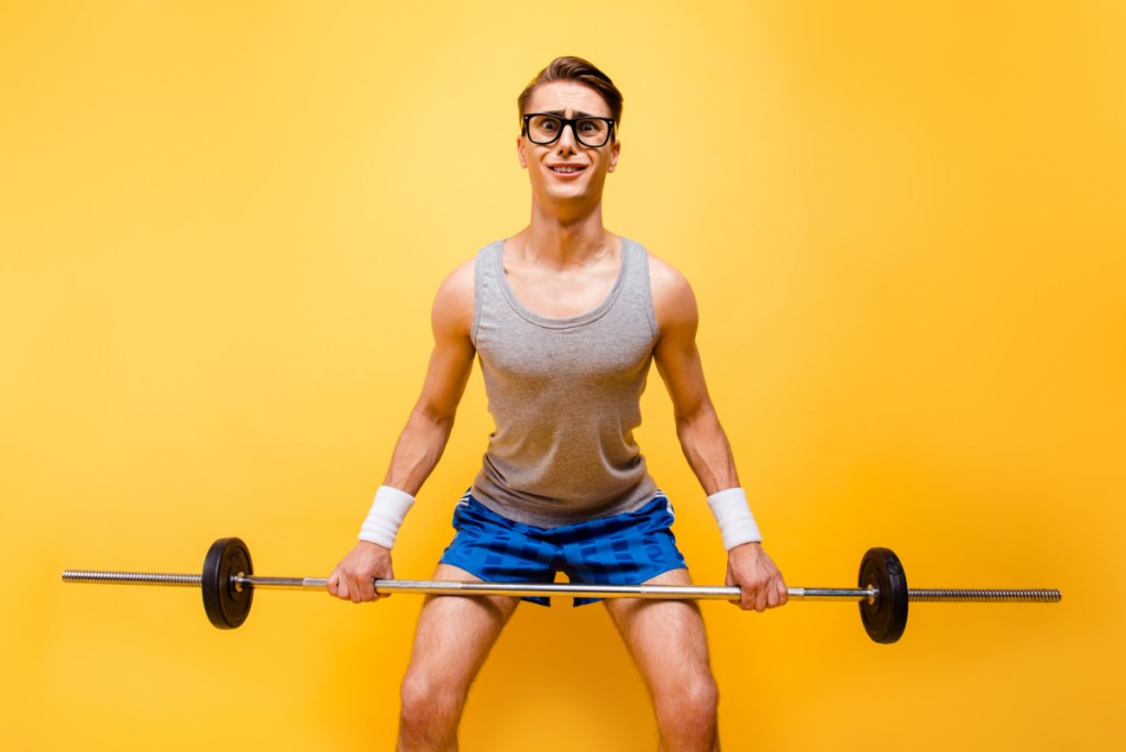 It seems I'm not in shape! Portrait of masculinity man with a confused and puzzled face can not lift a heavy barbell isolated on bright yellow background