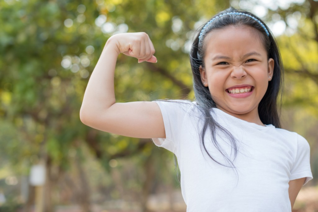 happy Little Asian girl child standing showing front teeth with big smile.  showing arms muscles smiling proudly. Looking camera showing biceps. fresh healthy green bio background. Fitness concept.