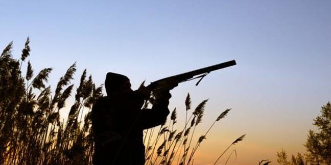 A silhouette of a hunter in a field aiming their gun.