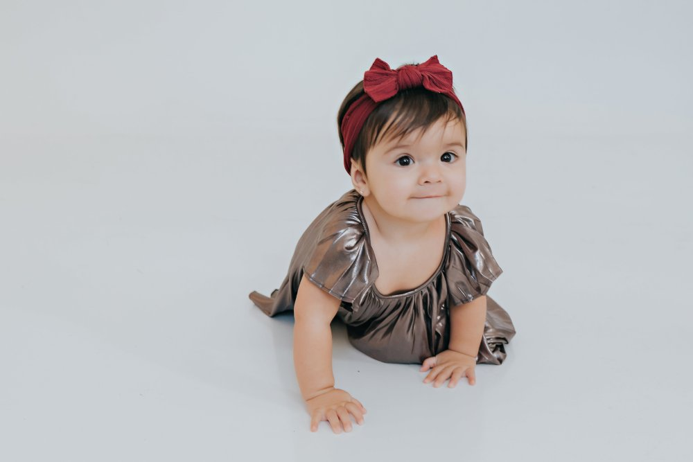 Our baby girl! She is always on the move! I love her metallic dress and it is perfect for any special occasion! You can change the hair accessory color to make it coordinate with anything! #girlsfashion #familyphotos #babygirloutfit #specialoccasion