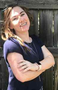 Lauren of Truly Devoted to Him laughing in sun leaning against wooden fence