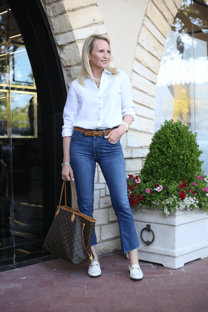 Dallas lifestyle blogger Megan Saustad wearing white linen shirt, Gucci loafers, Hermes belt and carrying Louis Vuitton Neverfull in monogram canvas.