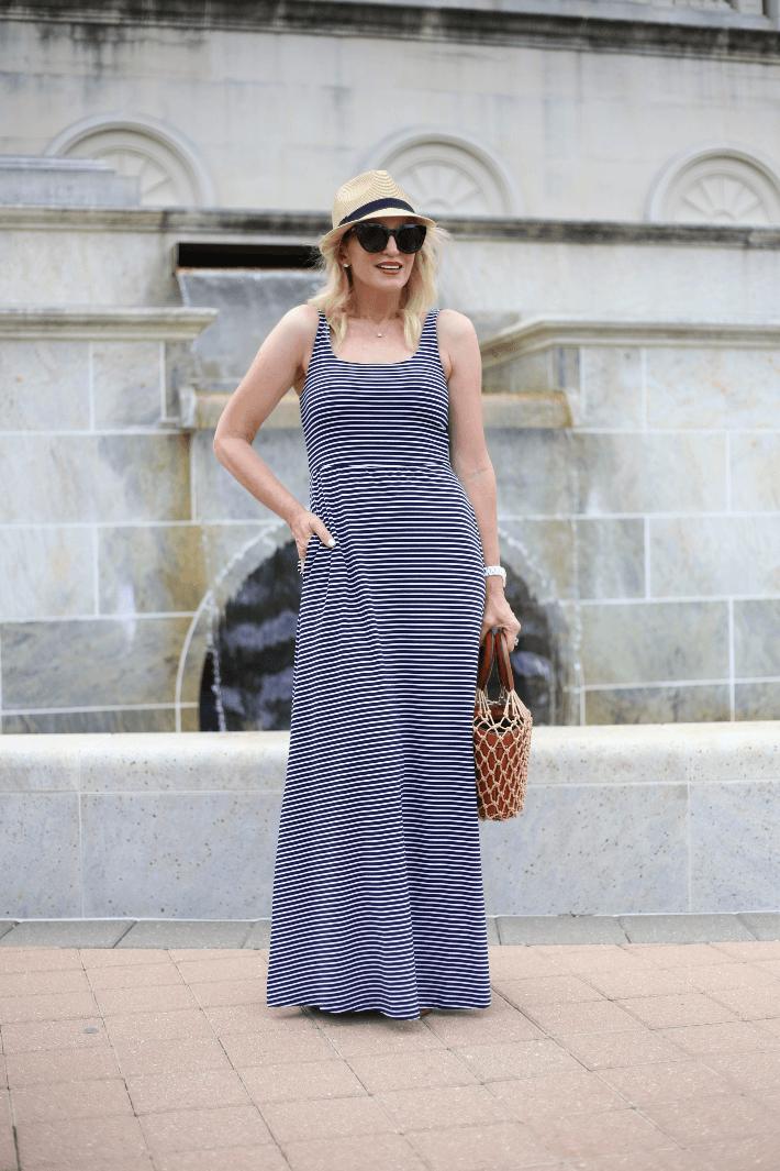 Dallas blogger Megan Saustad wearing Peach Ensenada stripe maxi dress and carrying Staud bucket bag.