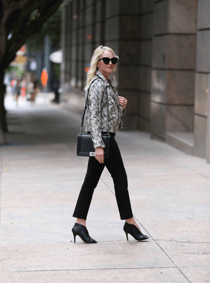 Style blogger wearing BlankNYC snake print moto jacket, carrying Chanel Boy Bag and wearing Black Rowen Booties.