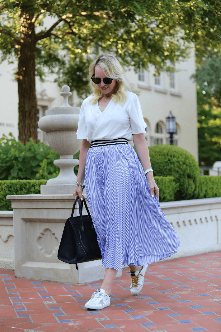 Blogger wearing Chicwish blue and white striped midi skirt, Golden Goose sneakers and carrying black Celine phantom handbag.