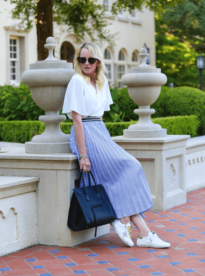 Style blogger Megan Saustad wearing Chicwish blue and white pleated midi skirt, Golden Goose sneakers, Quay Australia Sunglasses and carrying Celine Phantom handbag.