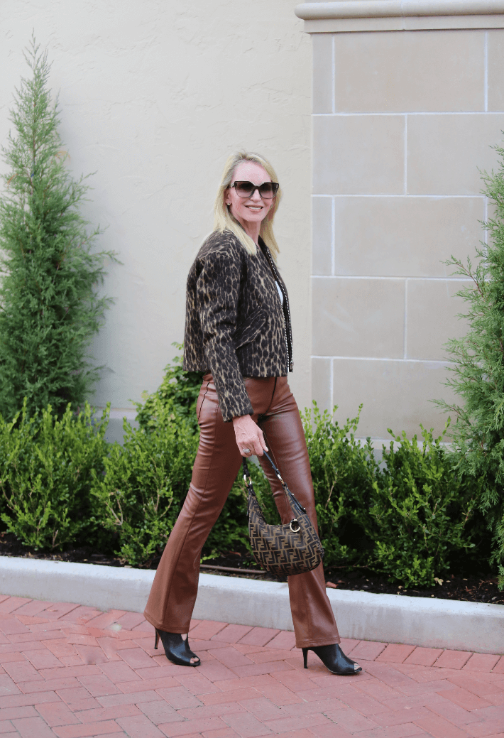 Fashion blogger Truly Megan wearing faux leather pants, leopard bomber and carrying Fendi bag.
