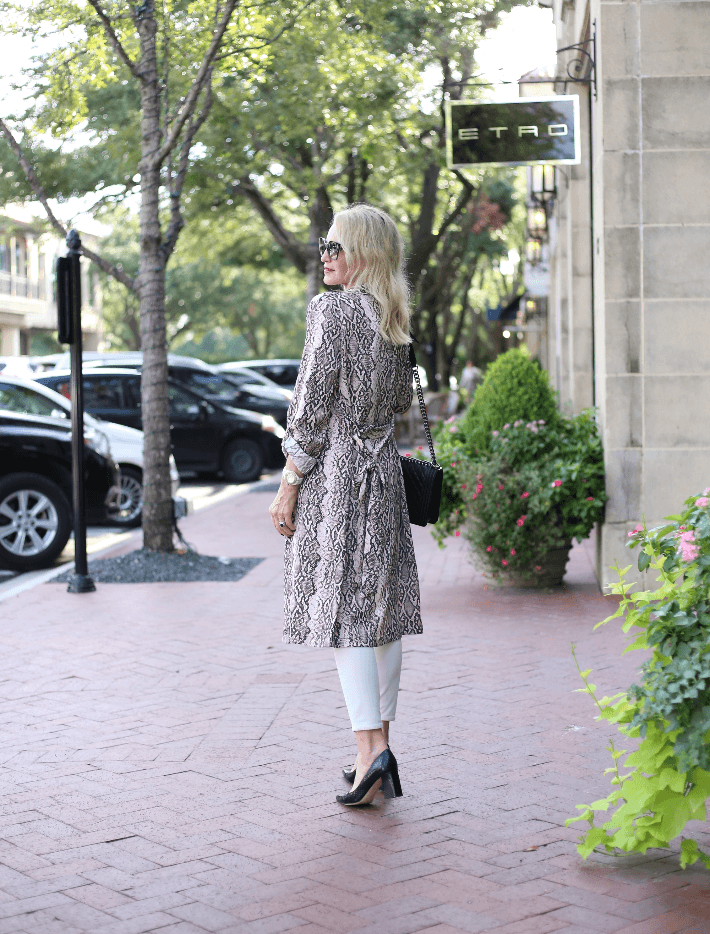 Blonde fashion blogger wearing snake print trench, skinny jeans, black pumps and carrying Chanel Boy Bag.