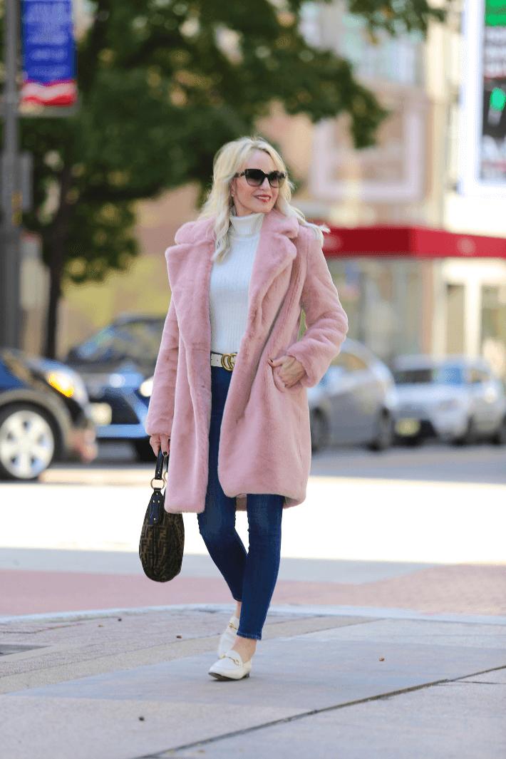 Dallas style blogger Truly Megan wearing Lovers + Friends Pink Faux Fur Coat, Gucci Brixton flats, Gucci belt, Prada sunglasses and carrying Fendi Zucca hobo handbag.