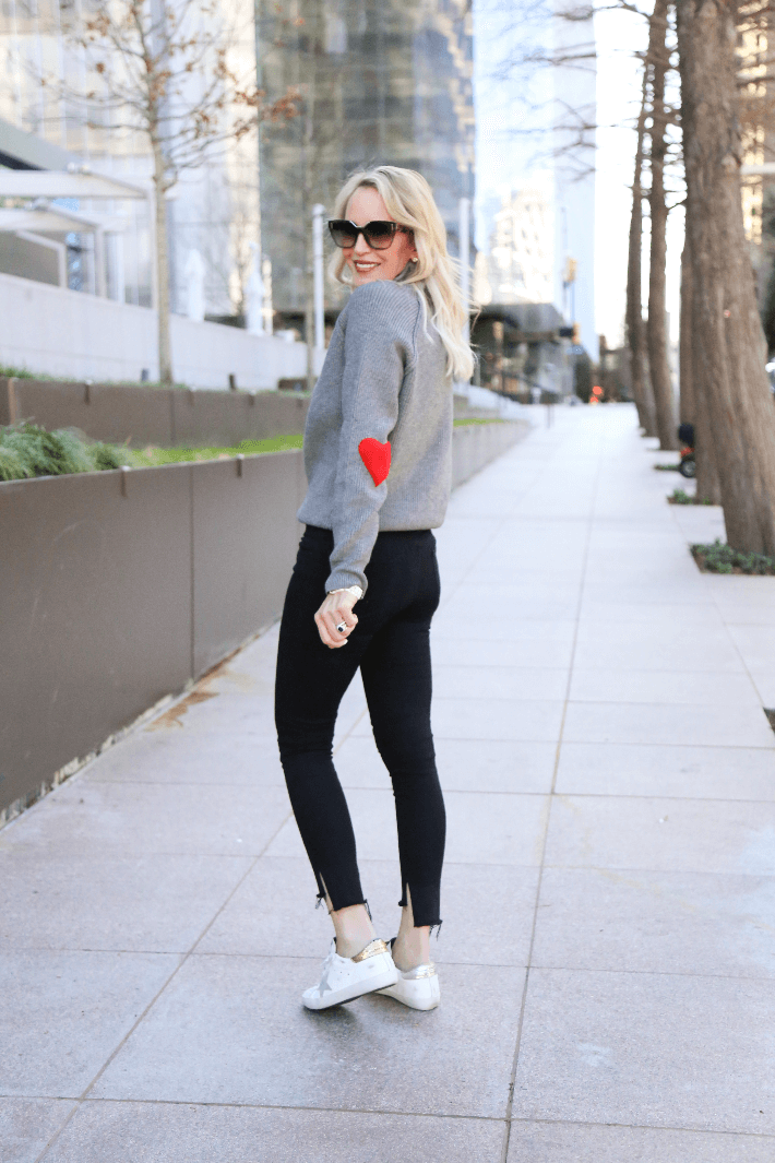 Dallas style blogger wearing Chicwish heart sleeve sweater, black jeans and Golden Goose deluxe sneakers in mix match style.
