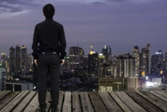 Business man standing on the platfrom and looking at night city