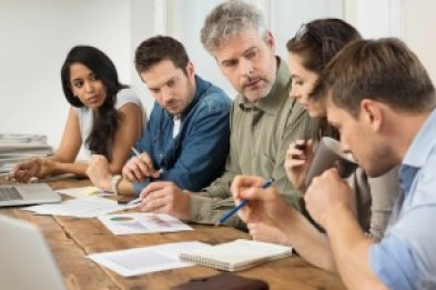 Businessman and woman discussing on stockmarket documents in office. Team of business people working together on paperwork. Office meeting of businesspeople at desk.