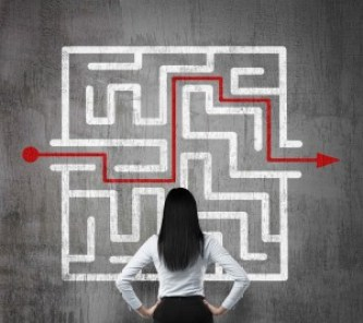 Rear view of the brunette girl who is looking at the solution of the maze. Concrete background.