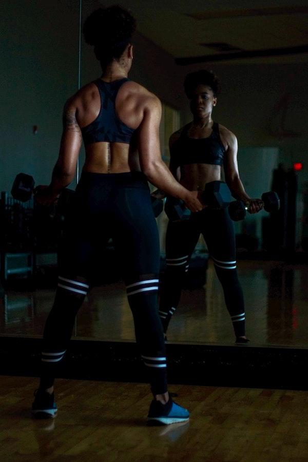 Woman lifting dumbbells at Equinox studio