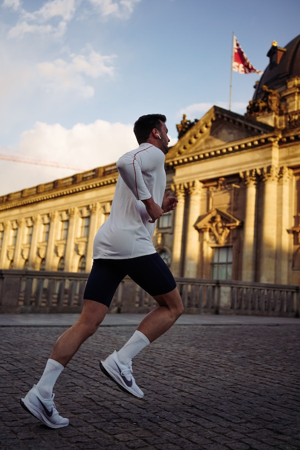 Man running past a large building in city
