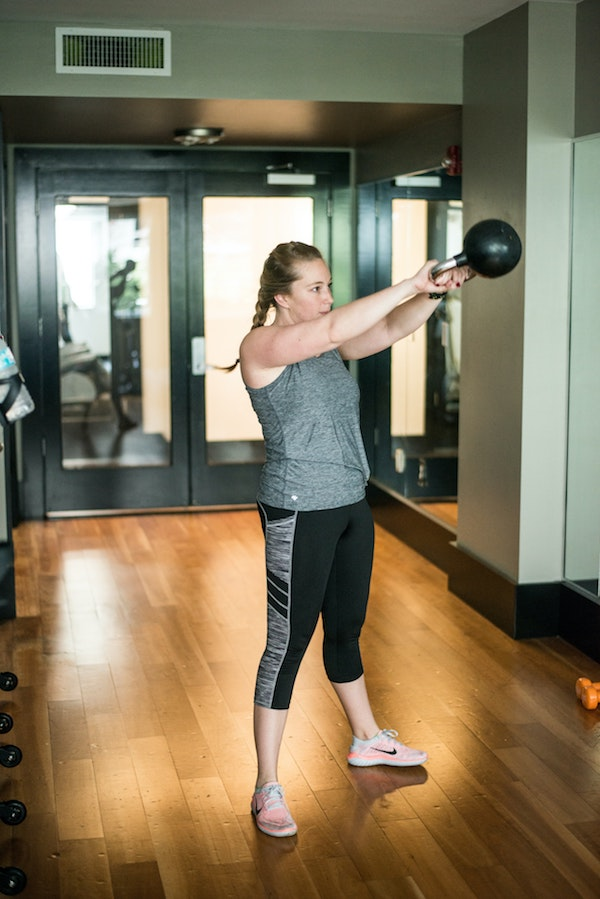 Woman doing kettlebell swing in gym