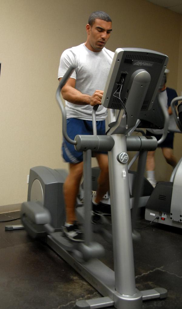 Man on an elliptical machine inside the gym