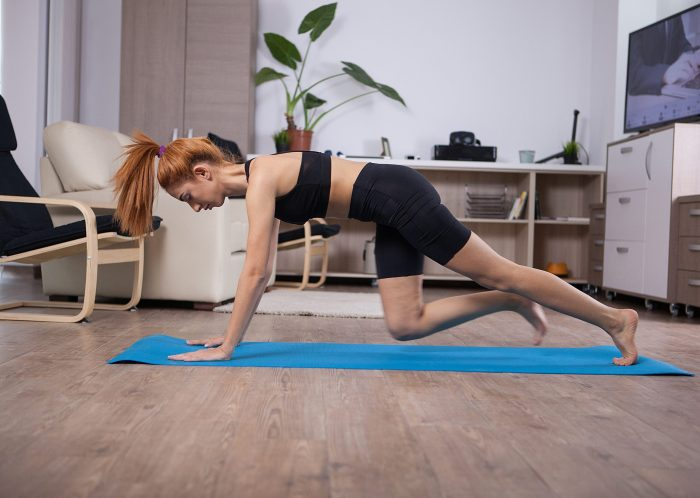 Woman working out on yoga mat at home