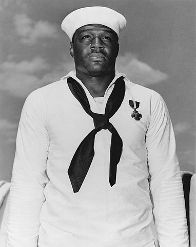 """Doris """"Dorie"""" Miller wears the Navy Cross, awarded for bravery during the Pearl Harbor attack. (Public Domain Photo)"""
