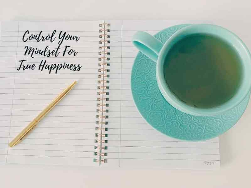 Control Your Mindset for true Happiness written in a notebook with Cup of TEA